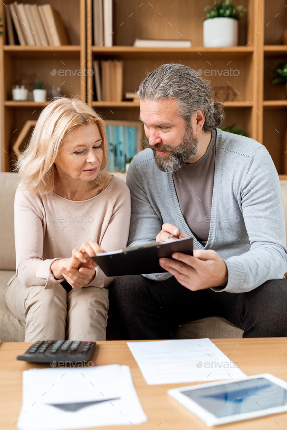 Mature man and woman reading terms of contract while going to buy new house - Stock Photo - Images
