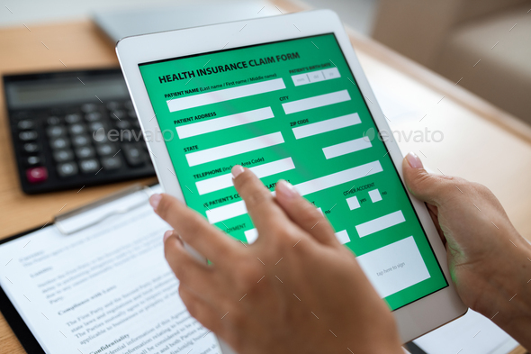 Electronic form of health insurance in digital tablet held by human hands - Stock Photo - Images