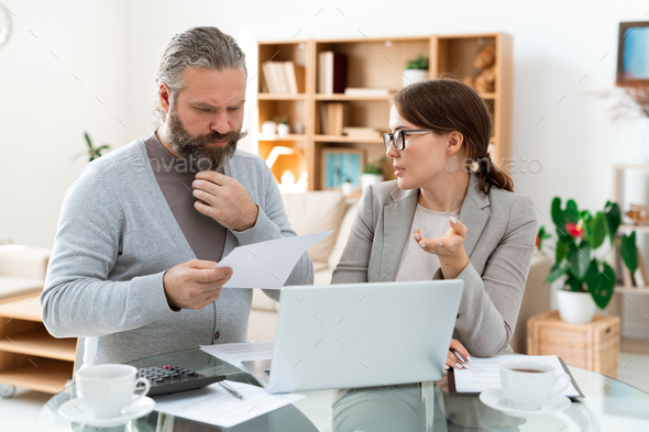 Pensive bearded man looking through paper while listening to real estate agent - Stock Photo - Images