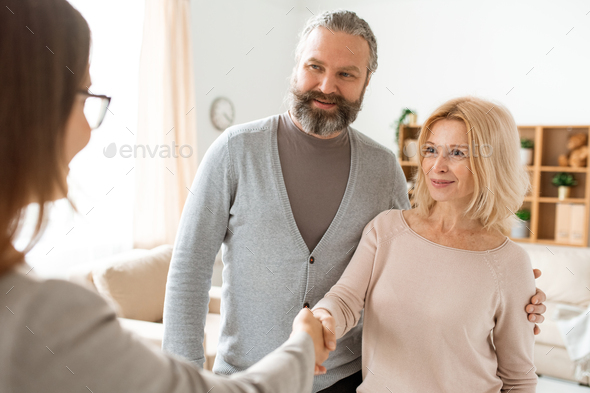 Happy mature couple welcoming their real estate agent at home - Stock Photo - Images