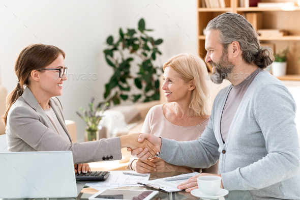Happy young real estate agent congratulating mature clients on successful deal - Stock Photo - Images