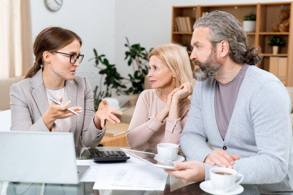 Mature couple and real estate agent discussing financial points - Stock Photo - Images