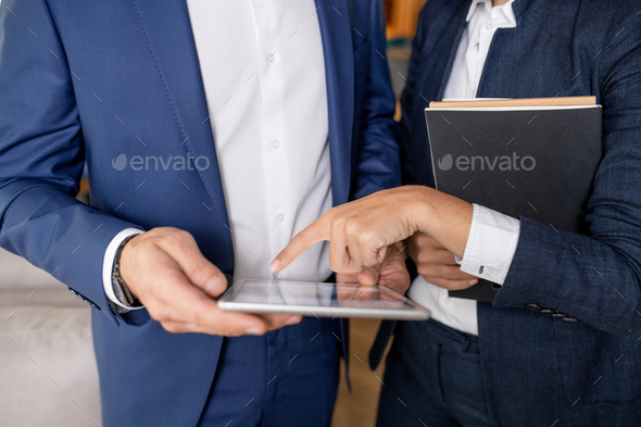 Elegant businesswoman discussing electronic document with businessman - Stock Photo - Images