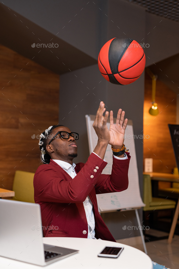 African guy throwing ball upwards while sitting by table in modern cafe - Stock Photo - Images