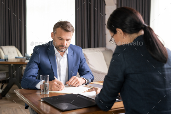 Serious businessman and his colleague working by table in restaurant - Stock Photo - Images