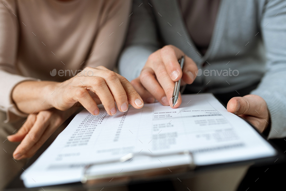 Two hands pointing at document while discussing terms and points of contract - Stock Photo - Images