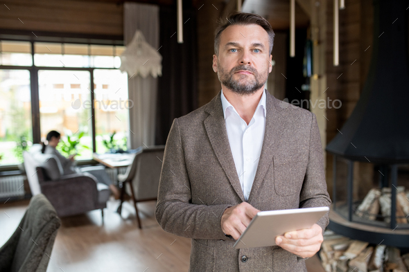 Serious middle aged businessman with beard scrolling in touchpad in restaurant - Stock Photo - Images