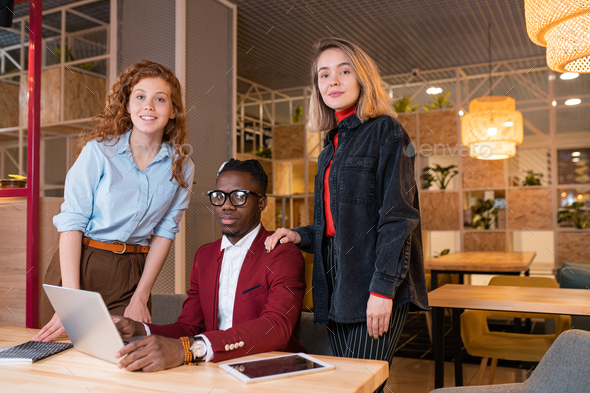 Small group of young successful intercultural employees looking at you - Stock Photo - Images