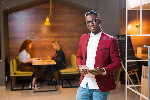 Young elegant man of African ethnicity in smart casualwear using digital tablet - Stock Photo - Images