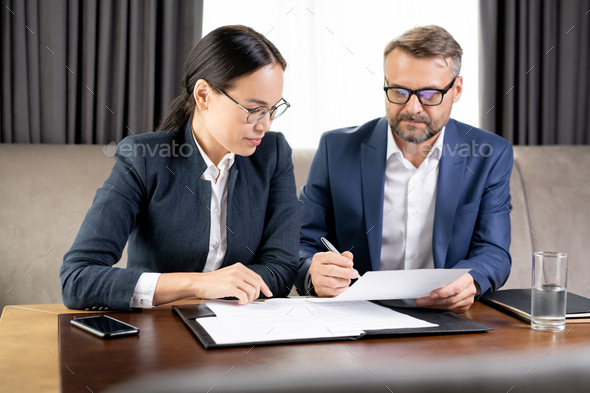 Confident businessman showing his business partner where to sign contract - Stock Photo - Images