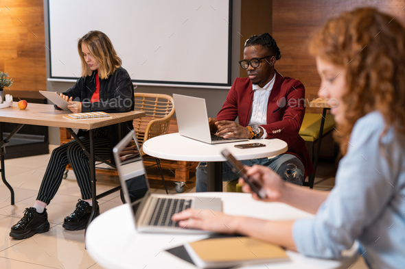 Group of multicultural students using mobile gadgets while preparing homework - Stock Photo - Images