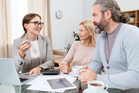 Young cheerful financial advisor or agent consulting mature husband and wife - Stock Photo - Images