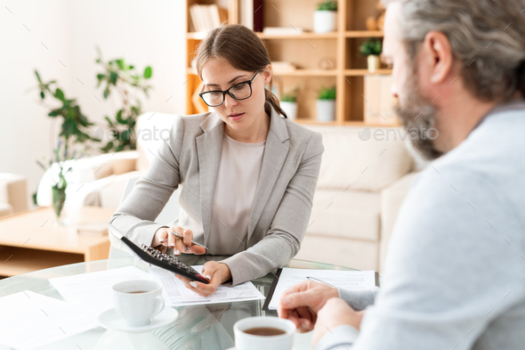 Young accountant with calculator pressing buttons and consulting with colleague - Stock Photo - Images