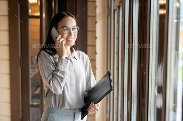 Happy young business agent with document and smartphone calling in restaurant - Stock Photo - Images