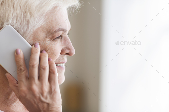 Side view of senior woman talking by phone - Stock Photo - Images