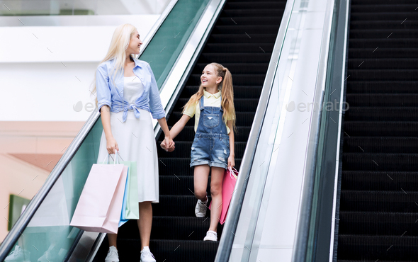 Mother And Little Daughter Standing On Escalator Shopping In Hypermarket - Stock Photo - Images