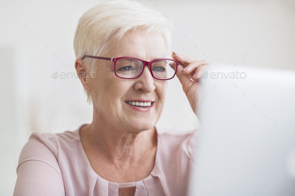 Senior business lady enjoying her new stylish eyewear - Stock Photo - Images