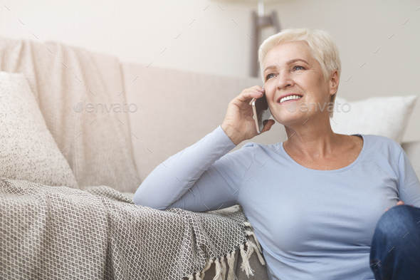 Happy female pensioner talking by phone at home - Stock Photo - Images