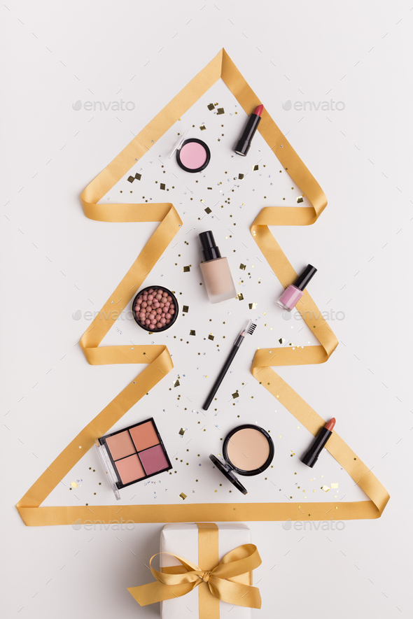 Pine tree of gold ribbon with decorative cosmetics inside - Stock Photo - Images
