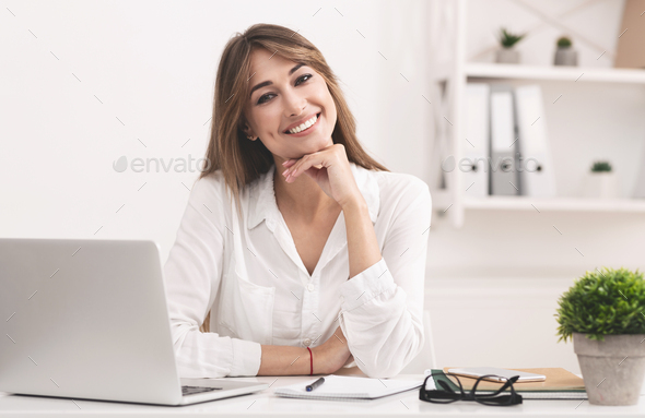 Smiling Businesswoman Sitting At Laptop Posing At Workplace - Stock Photo - Images