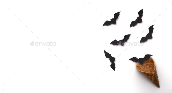 Halloween bats flying out of the waffle horn on white - Stock Photo - Images