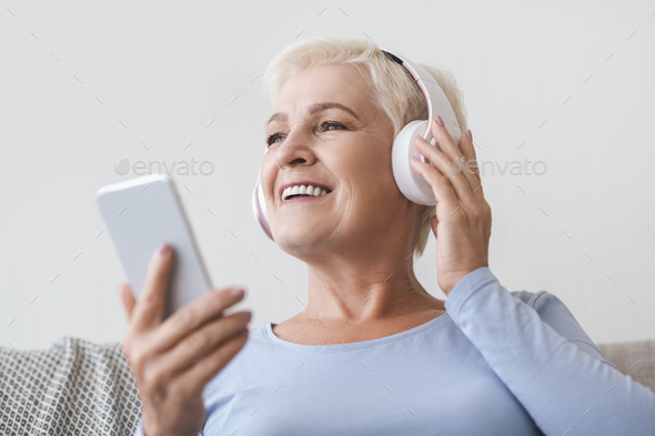Senior woman enjoying music and watching videos on smartphone - Stock Photo - Images