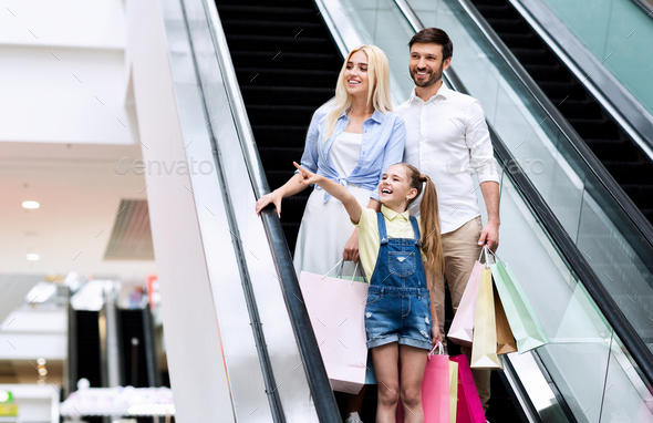 Daughter Pointing Finger Standing On Escalator With Parents In Mall - Stock Photo - Images