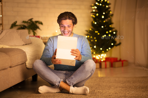 Handsome man opening gift box against Christmas Tree - Stock Photo - Images