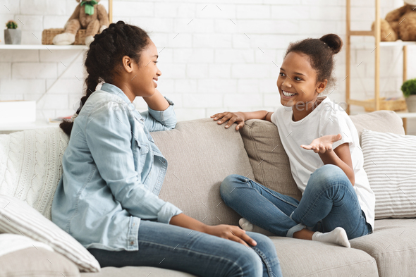 Two lovely black sisters having conversation at home - Stock Photo - Images