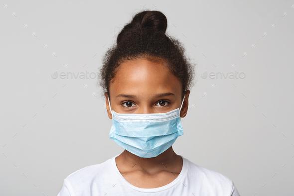 Portrait of little black girl wearing medical mask - Stock Photo - Images