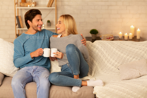Loving Couple Clanging Cups Together Sitting On Couch At Home - Stock Photo - Images