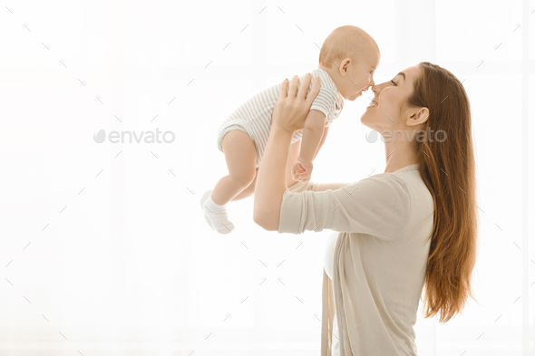 Mother touching noses with her baby while lifting him up - Stock Photo - Images