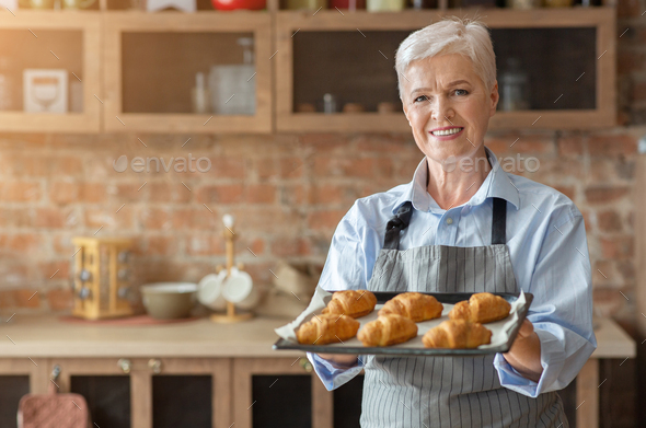 Happy old woman presenting tray with self made croissants - Stock Photo - Images