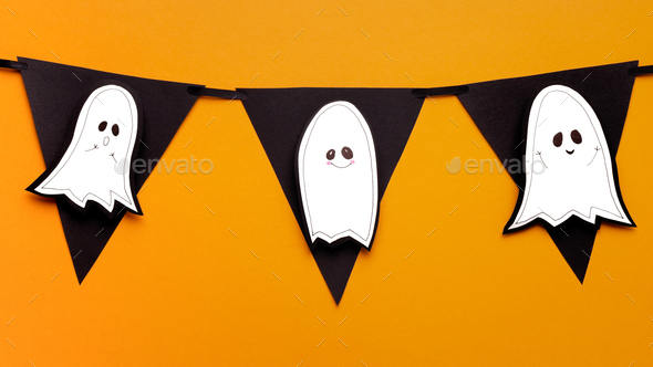 Close up of cute paper handicraft ghosts on black garland - Stock Photo - Images