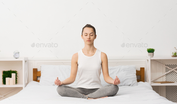 Young sporty woman practicing yoga after waking up - Stock Photo - Images