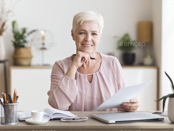 Smiling senior business woman working with documents at home - Stock Photo - Images