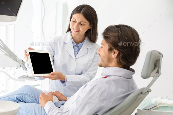 Female dentist doctor showing patient blank digital tablet screen - Stock Photo - Images