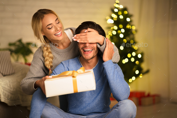Christmas gift. Happy woman making surprise to husband - Stock Photo - Images