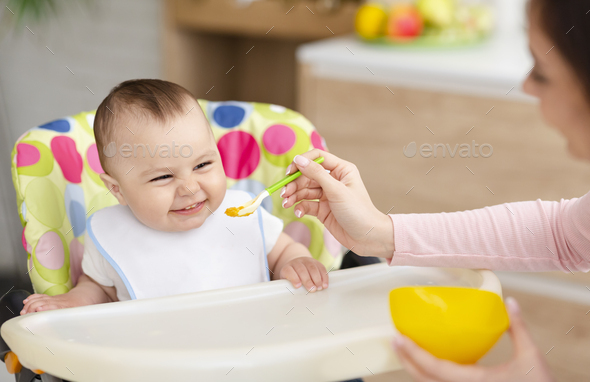 Cheerful baby eating in kitchen in high chair - Stock Photo - Images