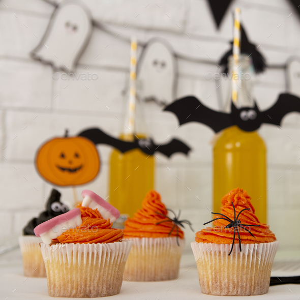 Halloween stylized yellow cocktails and cup cakes - Stock Photo - Images