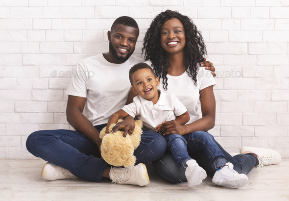 Young Black Parents And Their Son Sitting On Floor Together - Stock Photo - Images