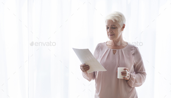 Old female author reading manuscript and drinking tea - Stock Photo - Images
