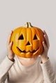 Woman holding smiling pumpkin at her head on gray - PhotoDune Item for Sale