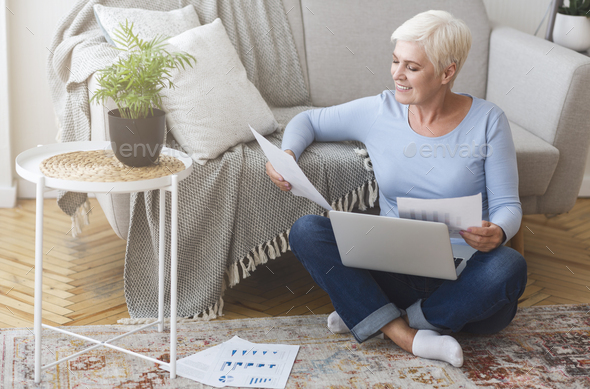 Senior financial consultant working with laptop at home - Stock Photo - Images