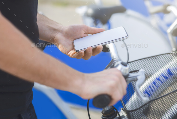 Man using GPS navigator in his phone cycling in city - Stock Photo - Images