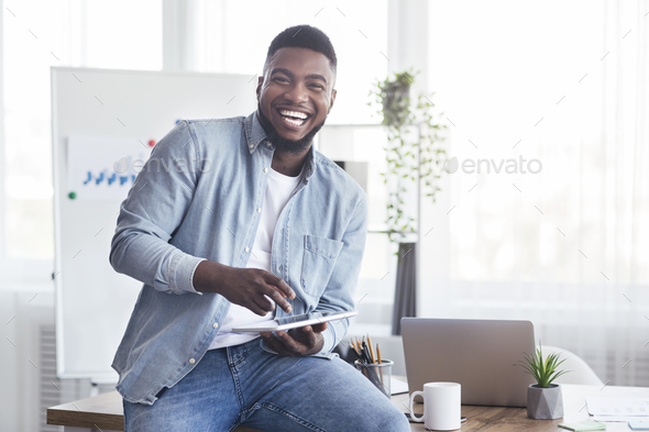 Cheerful black employee using digital tablet in office and laughing - Stock Photo - Images