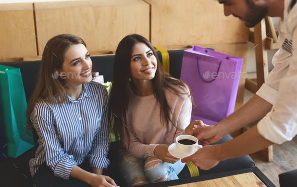 Waiter bring coffee for two cheerful girls in cafe after shopping - Stock Photo - Images