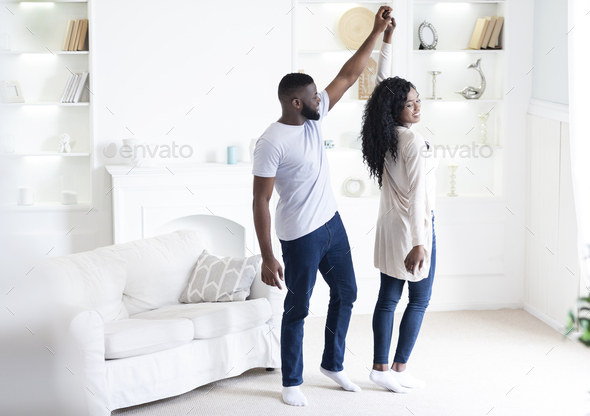 Romantic african american couple dancing at home, holding hands - Stock Photo - Images