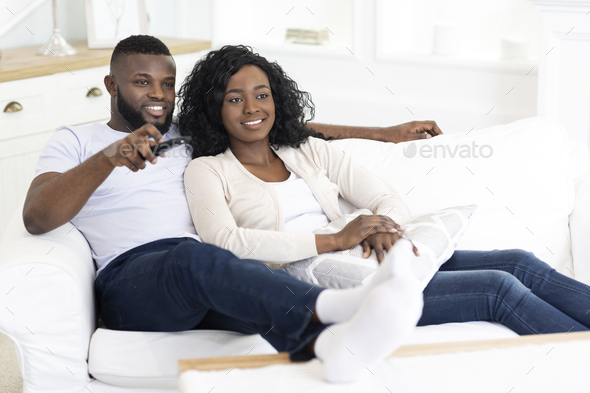 Afro couple relaxing on couch at home and watching tv - Stock Photo - Images
