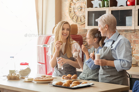 Beautiful family eating pastry with milk at kitchen - Stock Photo - Images